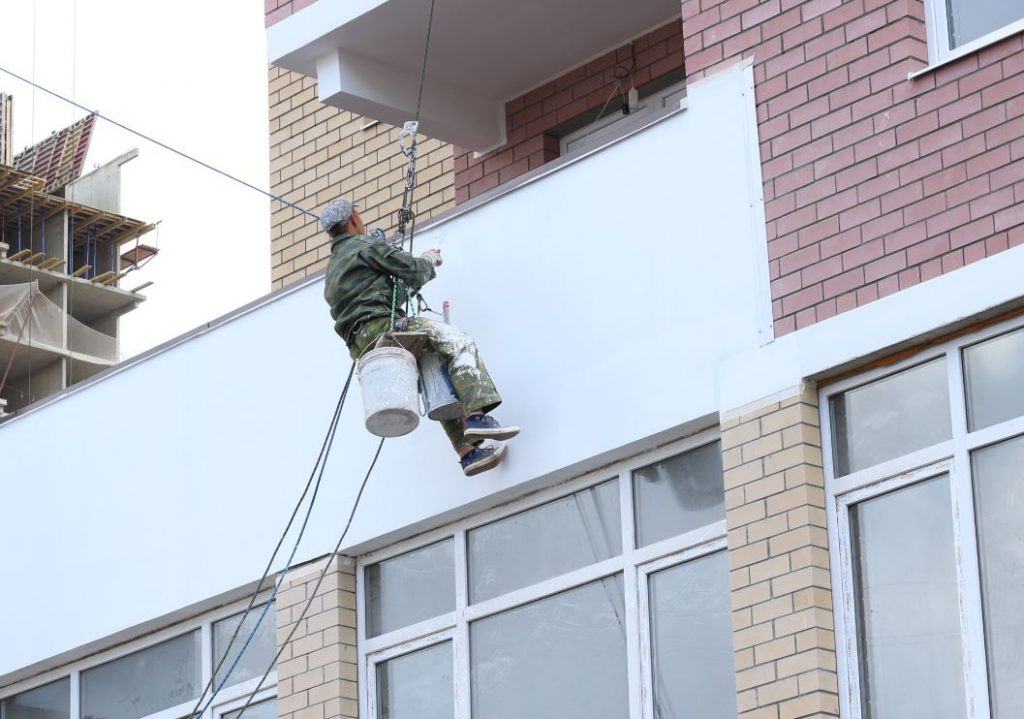 Man painting a facade on commercial business exterior